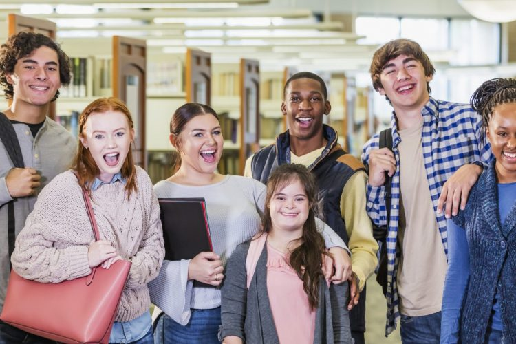 A multi-ethnic group of seven high school students, 15 to 17 years old, standing together in a library, smiling and looking at the camera. The girl in the middle has down syndrome.