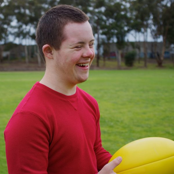 Sixteen-year-old boy smiling while holding football at park.