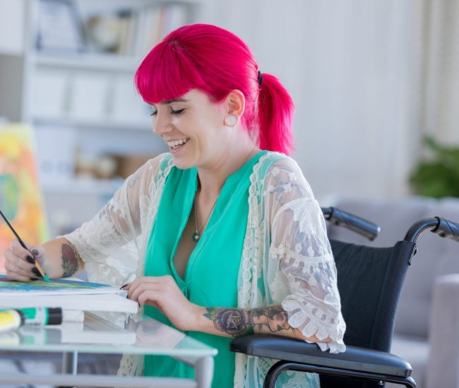 Trendy young woman with pink hair smiles while working on a painting. She is painting on a canvas. She is sitting in a wheelchair.